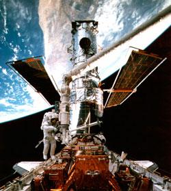 Romteleskopet Hubble veier over 11 tonn, og har fått påmontert en festeanordning som gjør at en rakett kan styrte det trygt ned i havet. På dette bildet besøkes Hubble av en romferge i 1997. (Foto: NASA)