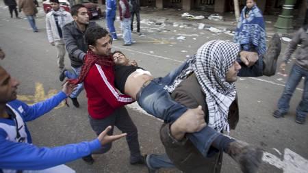 VOLDELIGE SAMMENSTØT: En skadet demonstrant hjelpes bort, nær Tahrir-plassen i Kairo. (Foto: Bernat Armangue/Ap)