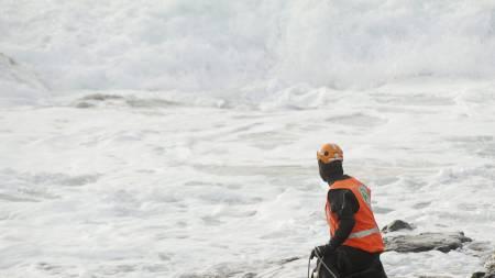 En av redningsarbeiderne gjør strandsøk der de to savnede filmskaperne forsvant i sjøen. (Foto: GUNNAR KVASSHEIM/Afp)