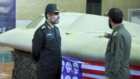 DRONE: Representanter for Irans militære står ved siden av droneflyet   de hevder å ha skutt ned. Dronen skal tilhøre USA. (Foto: HANDOUT/Reuters)