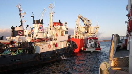 GIKK PÅ GRUNN: Her får containerskipet Svealand assistanse fra en slepebåt etter grunnstøtingen. (Foto: Redningsselskapet)