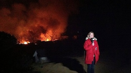 BYEN BRENNER: Reporter Elin Sørsdahl rapporterer hjem om de katastrofale ødeleggelsene etter jordskjelvet og tsunamien. I bakgrunnen ser man flammene fra byen Kesennuma. (Foto: Santiago Vergara)