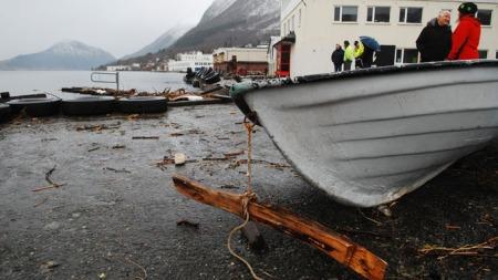 BÅT SLENGT PÅ LAND: Denne båten ble slengt på land på kaien i Ørsta. Flytebryggen i bakgrunnen er knust til pinneved.  (Foto: Kjell Arne Steinsvik / Møre-Nytt)