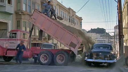 Hindringene er mange og bokstavelige når det begynner å gå unna i biljakten gjennom San Franciscos bratte gater. Passasjerene i den gamle limousinen sitter rimelig beskyttet mot gruslasset fra denne Peterbilten, verre er det med de i den åpne Cadillacen. Foto: Imcdb.org