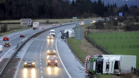 LASTEBILER BLÅSTE AV VEIEN: Emil har gjort stor skade i Storbritannia.   Her har to lastebiler blåst av veien på motorveien M9 nær Stirling i   Skotland. (Foto: RUSSELL CHEYNE/Reuters)