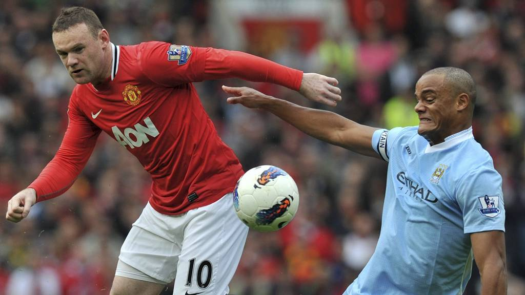Manchester City's Vincent Kompany tackles Manchester United's Wayne Rooney (Foto: Martin Rickett/Pa Photos)