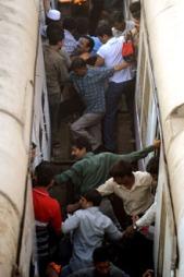 Indiske pendlere forsøker å klatre fra et tog til et annet i rush-trafikken.  (Foto: Afp)
