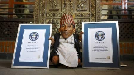 BEVISENE: Chandra Bahadur Dangi poserer med diplomene fra Guinness. (Foto: NAVESH CHITRAKAR/Reuters)