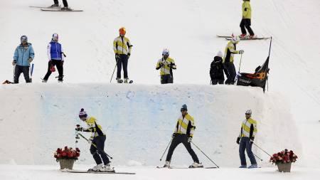 Medlemmer fra det kanadiske skicrosslaget står ved hoppt i Grindelwald der lagkameraten Nick Zoricic omkom lørdag. (Foto: FABRICE COFFRINI/Afp)