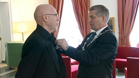MEDALJE: Torbjørn Pettersen ble hedret av ordfører Tor Opdal Hansen (H) med Kongens fortjenstmedalje i sølv. (Foto: TV 2)