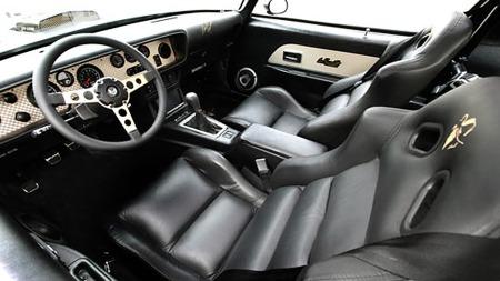 Det klassiske dashboardet og rattet er stort sett urørt, men dørsidene er oppgradert og bilen har fått seriøse racingstoler med Burt Reynolds rollefigur Bandits siluett innbrodert. Foto: Year One