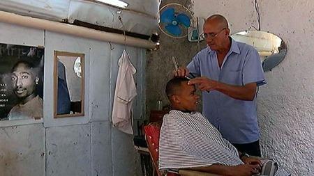 HVERDAGSLIV: Kommunistpartiet på Cuba har etter hvert åpnet opp for at cubanere kan starte små, private bedrifter. Her får en mann klippet håret av en frisør i Havana. (Foto: Santiago Vergara/TV 2)