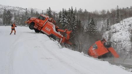KOM SEG UT: Her kan du sjå at bergingsmann Arnt Ove Brattbakk, til venstre i biletet,  akkurat kom seg ut av bilen sin før den vert dradd ned den stupbratte skråningen.  (Foto: Gunn Iren Johnsrud)