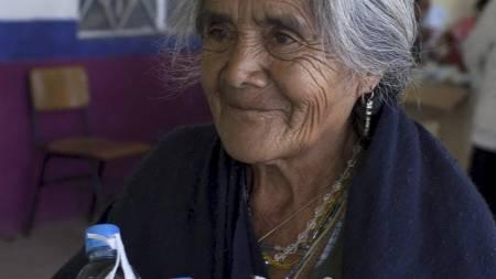 En kvinne har fått utlevert ansiktsmasker og vannflasker for å kunne være forberedt ved et vulkanutbrudd. (Foto: Dieu Nalio Chery/Ap)