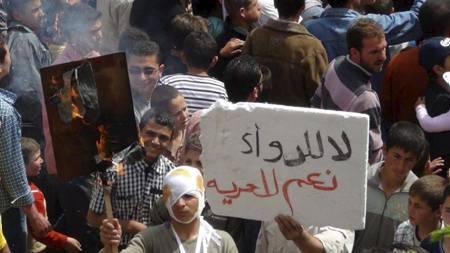 RASER: En mann brenner en plakat med bilde av Syrias president Bashar al-Assad under en demonstrasjon i Tabliseh nær byen Homs i de midtre delene av Syria. Væpnede menn har sprengt en oljerørledning øst i Syria, meldte det statlige nyhetsbyrået SANAA lørdag. Den politiske opposisjonen gjentar sitt krav om at FN må gripe inn militært for å få slutt på volden i landet. (Foto: Nettverket Shaam / Reuters / NTB scanpix/Reuters)