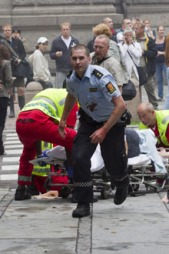 Her er politimannen Simon avbildet like etter at han har fraktet   24-åringen til ambulansen. (Foto: Scanpix)