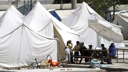 Syriske flyktninger sitter utenfor telt i Reyhanli-leiren i provinsen Hatay sør i Tyrkia. (Foto: MURAD SEZER/Reuters)