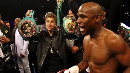 Justin Bieber bærer inn beltene til Floyd Mayweather jr. før kampen i Las Vegas. (Foto: AL BELLO/Afp)