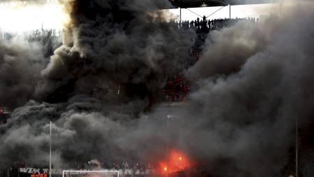 Politiet måtte inn på banen da det ble klart at Köln rykket ned fra Bundesliga. Fansen var langt fra fornøyde og røykla tribunene med sort røyk. (Foto: THOMAS BOHLEN/Reuters)