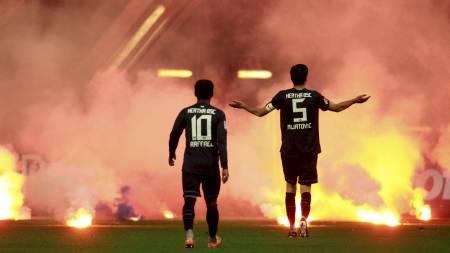 BER FANSEN ROE SEG: Raffael og lagkaptein Andre Mijatovic prøver å få Hertha Berlin-fansen til å slutte å kaste bluss inn på banen. (Foto: INA FASSBENDER/Reuters)