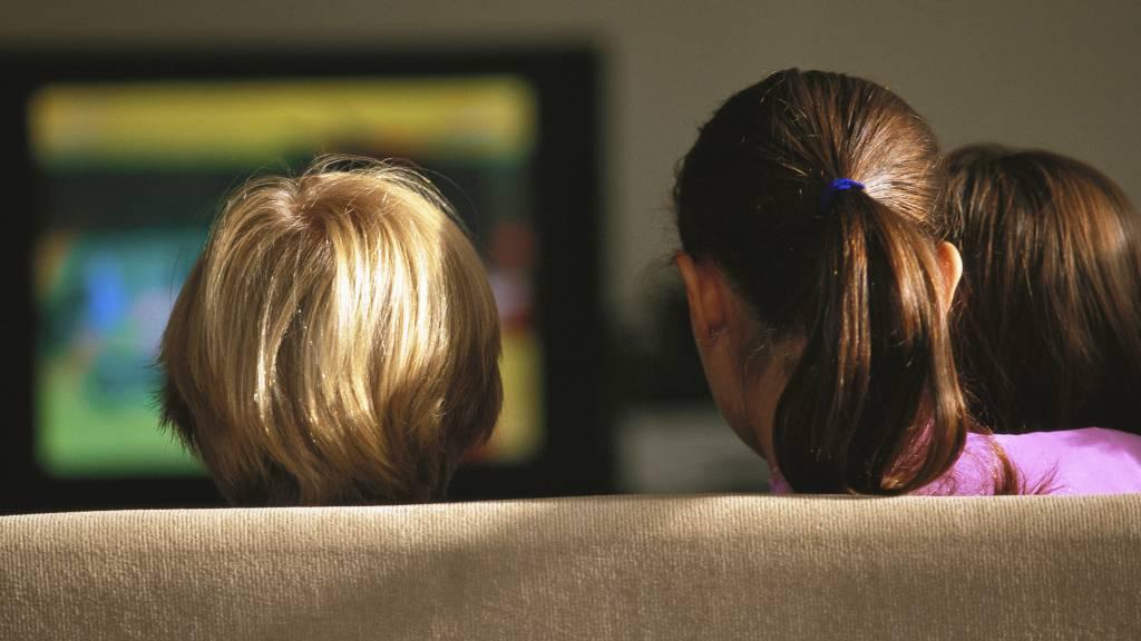 NEGATIV EFFEKT: Barn putter mer junk food i munnen hvis de sitter mye foran TV-skjermen, ifølge en ny amerikansk undersøkelse. (Foto: Illustrasjonbilde / Colourbox/Gerard Launet / PhotoAlto)