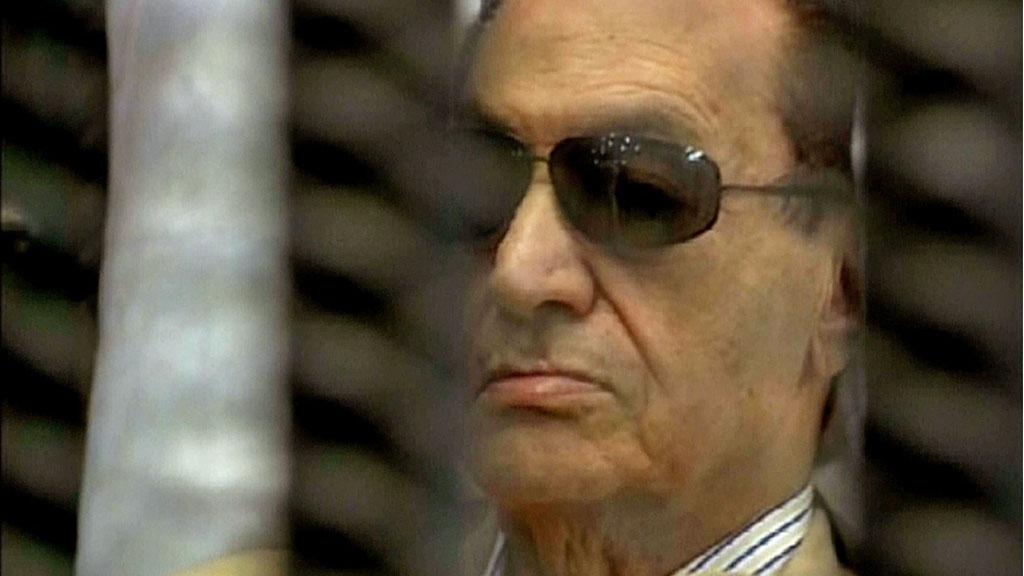 Et bilde hentet fra den egyptiske statskanalen viser egypts president Hosni Mubarak sittende inni et bur i rettssalen, mens dommen blir forkynt i Kairo lørdag morgen.  (Foto: AFP)