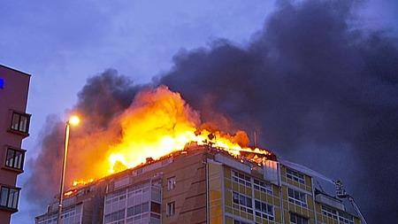 BRANNINFERNO: Det brant kraftig i toppetasjen på boligblokken på Grønland i Oslo lørdag kveld.  (Foto: Magnus Nøkland/TV 2)