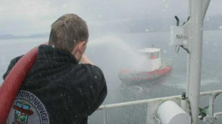 SLÅSS: Miljøvernforbundet spylte oppdretterne med brannslange da de tok kabelen mellom ubåten og «Miljødronningen».  (Foto: Miljøvernforbundet)