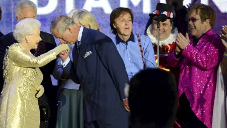 Prince Charles kisses the hand of Britain's Queen Elizabeth II on stage as British singers Paul McCartney (3rdR) and Elton John (Foto: LEON NEAL/Afp)