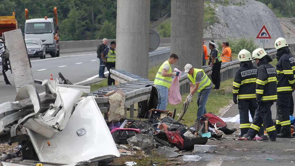 FLERE DREPT: Brannmenn og politi rydder opp på ulykkesstedet. (Foto: Afp)