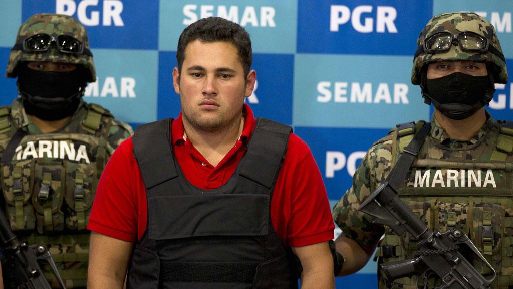 TABBE: Her vises den uskyldige bilselgeren fram som et trofé, mens tungt bevæpnede spesialsoldater står maskert ved siden. (Foto: Eduardo Verdugo/AP)