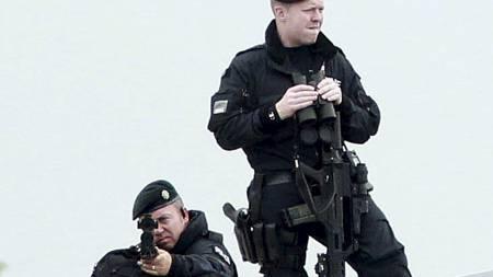 STRENGT SIKKERHETSOPPLEGG: Væpnet politi holdt utkikk på taket til teateret der Dronning Elisabeth II og Martin McGuinness møttes onsdag. (Foto: PETER MUHLY/Afp)