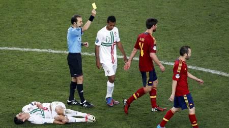 Xabi Alonso har felt Cristiano Ronaldo og får gult kort. (Foto:   Darko Vojinovic/Ap)