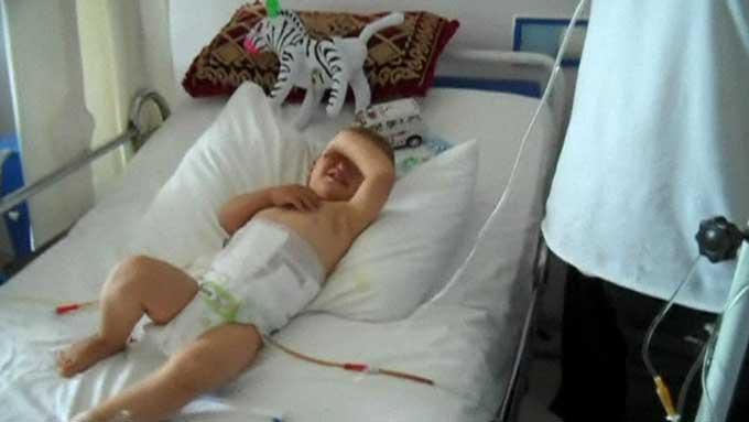 ROPER PÅ MAMMA: En to år gammel syrisk gutt blir behandlet på sykehus i Tyrkia. Familien forteller at han ble truffet av en granatsplint i magen. (Foto: CBS)