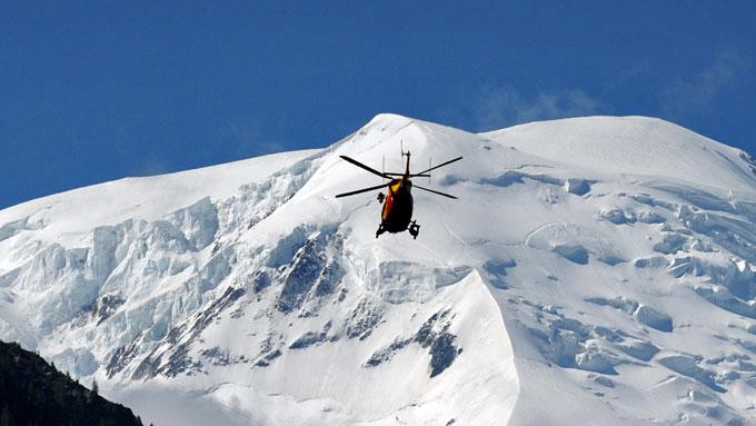 DØDELIG SNØSKRED: Redningsmannskap i helikopter over Mont Blanc-massivet hvor et snøskred tok livet av minst seks personer torsdag. (Foto: Jean-Pierre Clatot/AFP)