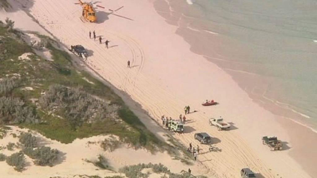 DREPT AV HAI: Et redningshelikopter og andre redningsmannskaper på stranden Wedge Island nord for den australske byen Perth - hvor en surfer ble angrepet og drept av en hai lørdag. (Foto: STRINGER/AUSTRALIA/Reuters)