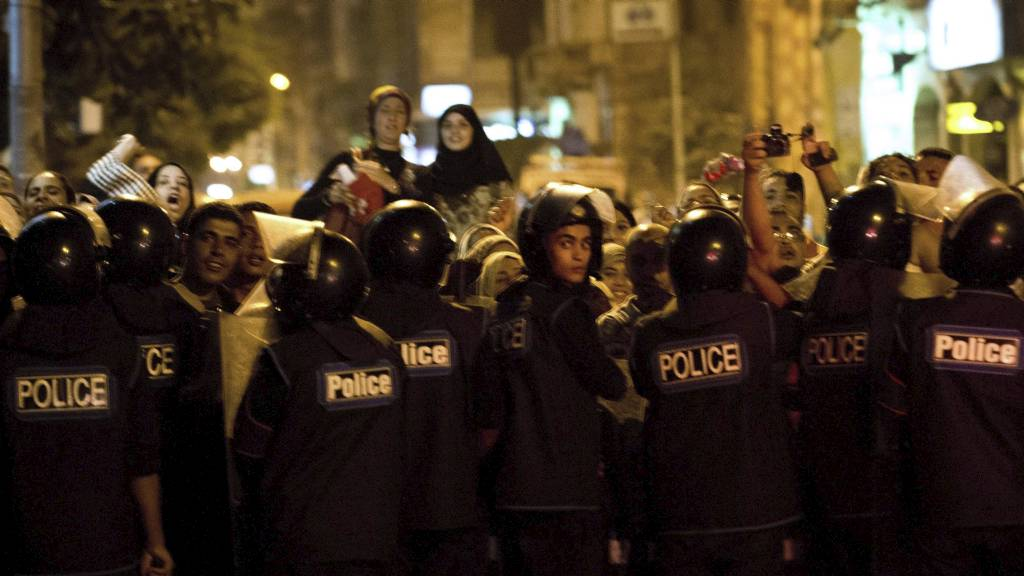 DEMONTERTE: Opprørspoliti holder kontroll på demonstranter som demonstrerte mot Hillary Clintons besøk i Egypt. (Foto: BRENDAN SMIALOWSKI/Afp)