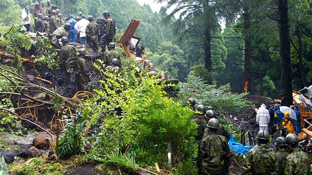 JORDSKRED: Japanske soldater leter gjennom jordmassene etter savnede blant raserte hus etter de enorme nedbørsmengdene utløste et jordskred fredag. (Foto: HANDOUT/Reuters)