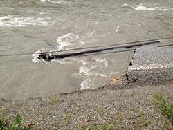 Flomvannet tok med seg både veien og telefonstolpene. (Foto:   Egil Pettersen)