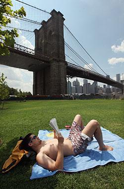 Isaac O'neill nyter sommerværet i Brooklyn Bridge Park mandag. (Foto: Afp)