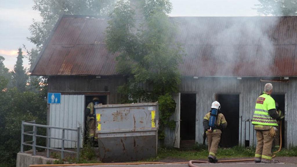 RYKKET TIL BRANN: Politi og brannvesenet rykket ut til brann i dette uthuset. Her fant de 26-åringen med mindre skader. Den døde mannen ble funnet i veikanten like ved. (Foto: Stener Kalberg)