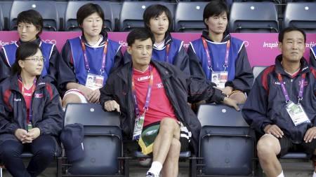 Nord-Koreas trener Gun Sin Ui (i midten fremme) sitter på lagets benk på Hampden Park og er lite blid etter at OL-kampen mot Colombia ble utsatt etter at det sørkoreanske flagget dukket opp da de nordkoreanske spillerne ble presentert. (Foto: GRAHAM STUART/Afp)