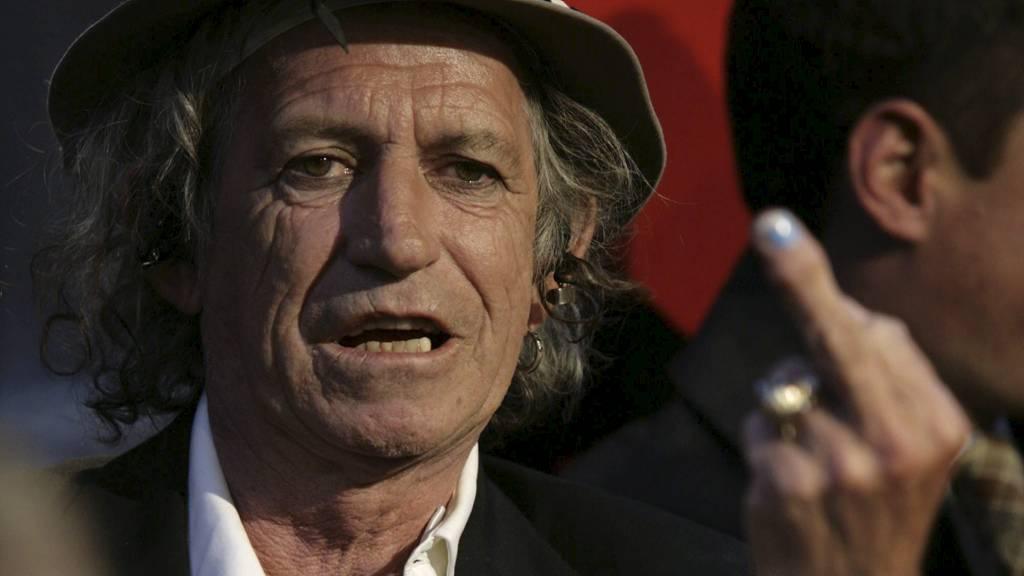 ELDGAMMEL: Gesten med å vise fingeren skriver seg helt tilbake til antikkens Hellas. Her er det Rolling Stones-gitarist Keith Richards som gjør stas på fotografene på premierevisningen til konsertfilmen «Shine A Light». (Foto: NICHOLAS ROBERTS/AFP)