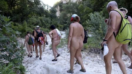 NAKENVANDRING: Nå er det slutt på nakenbading. Nakenvandring   er det nye for disse nudistene. (Foto: PHILIPPE DESMAZES/Afp)