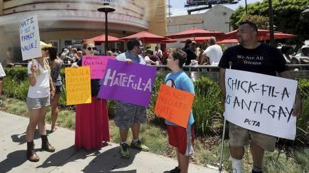 Mens køene er lange, står motstanderne på fortauet utenfor med sine plakater. (Foto: ROBYN BECK/Afp)