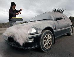 ASKE: Vic Cassin koster aske av bilen sin et stykke borte fra Mount Tongariro som hadde utbrudd mandag kveld. (Foto: Ap)