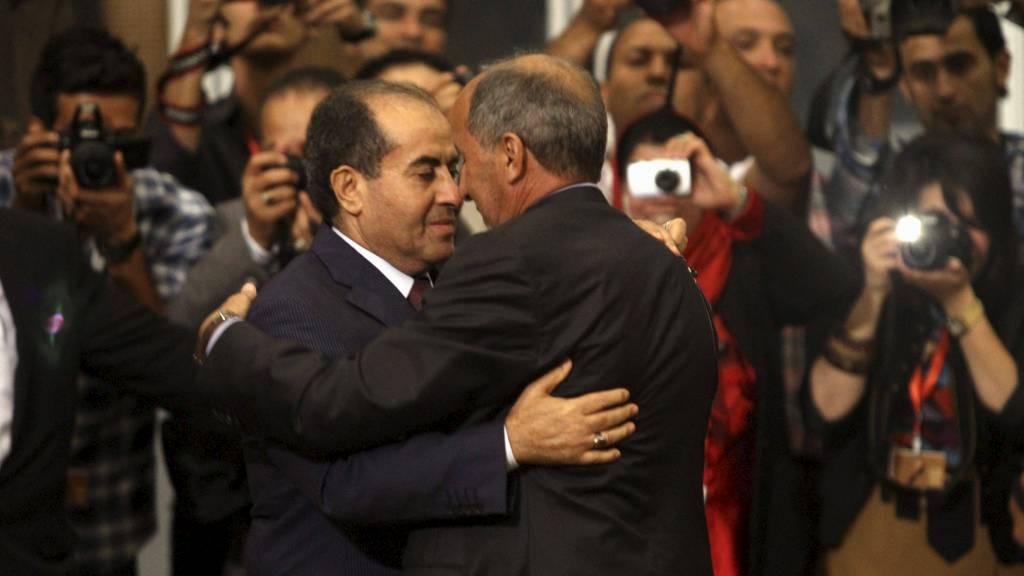 Lederen i det nasjonale overgangsrådet, Mustafa Abdel Jalil (t.h.) omfavner Mahmoud Jibril, som har vært statsminister under krigen i Libya. Det ble en svært følelsesladet kveld for flere. (Foto: ESAM OMRAN AL-FETORI/Reuters)