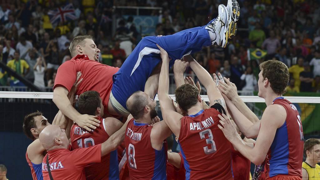VLADIMIR ALEKNO: Blir kastet i luften etter gullmedalje til det russiske laget i volleyball. (Foto: MANAN VATSYAYANA/Afp)