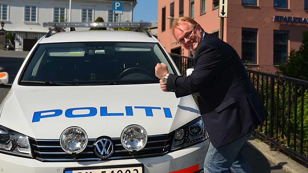 Justiskomiteens leder Per Sandberg (Frp) foran politibil i Arendal. (Foto: Ingvil Teige Stiegler/ TV 2)
