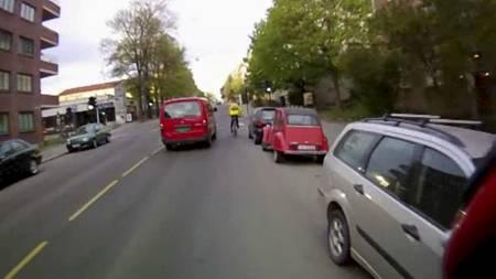 PRESSER SEG FORBI: En utålmodig og tutende kassebilfører presser seg forbi en syklist rett ved en trafikkøy og en rad av parkerte biler. (Foto: Morten H. Lode/)